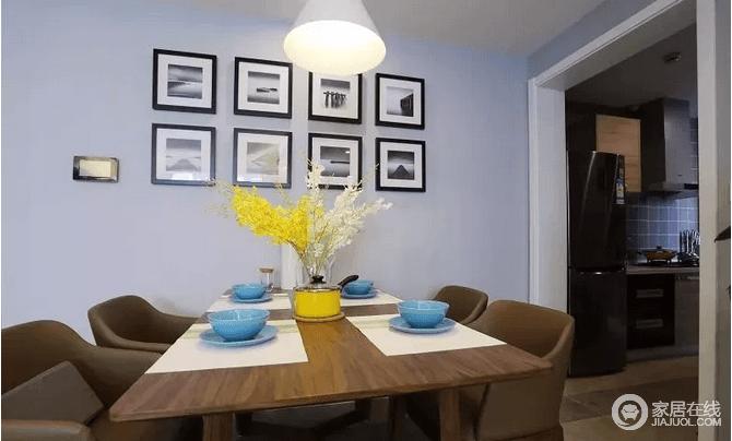 餐厅背景墙挂上一组黑白灰的装饰画,原木质感的餐桌,搭配舒适的餐椅,让整个空间多了自然温实;蓝色餐盘与黄色花卉的搭配下,显得简单而又充满了色彩感。