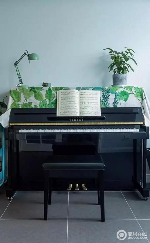 黑色钢琴上铺有带有绿色植物图案的桌布,好看得很!
