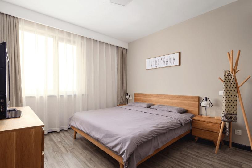 床头背景采用的是米色的纯色壁纸,跟原木色的家具搭配,显得卧室温暖,踏实