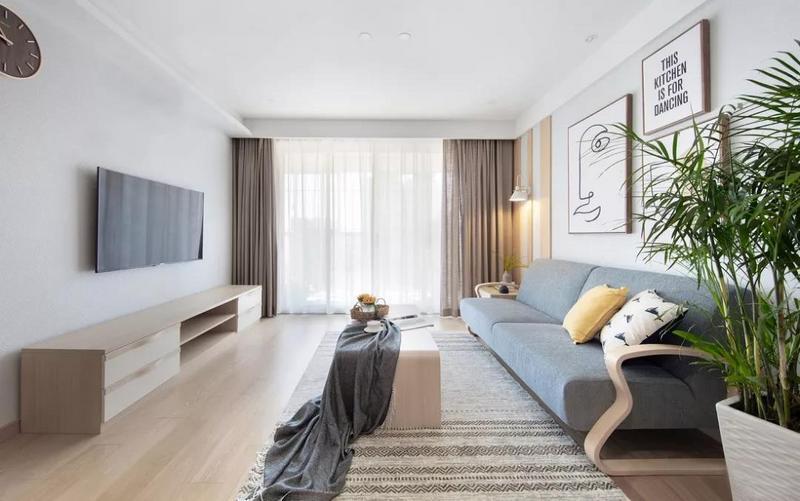 客厅以原木与白为主色调,大大的落地窗带来良好的采光,共同营造敞亮明净的空间氛围。