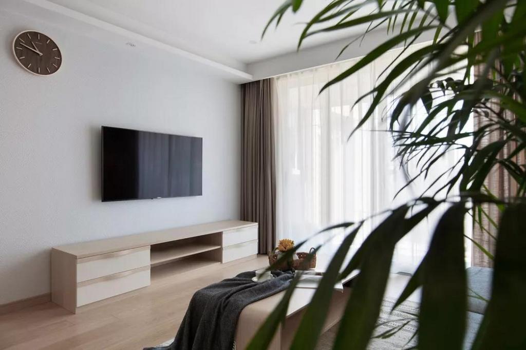 电视墙采用留白设计,保持墙面的纯净与包容。黑白时钟简约别致,提升空间气质。
