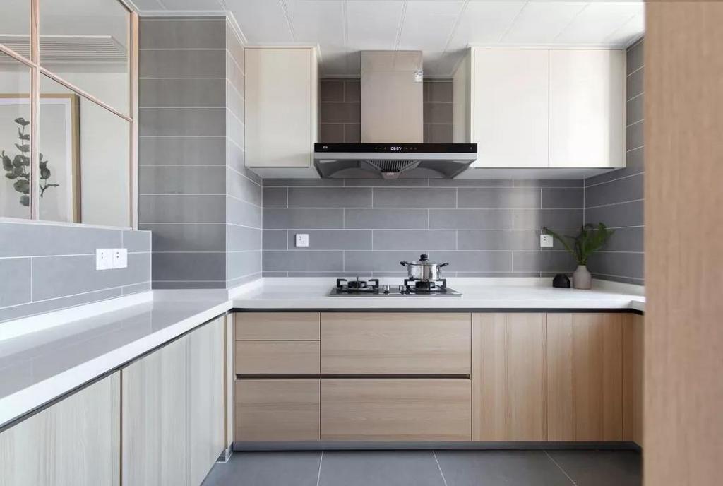 厨房墙地面通铺灰色瓷砖,白色操作台面干净明亮,木质橱柜的自然温润平衡灰色带来的清冷感。