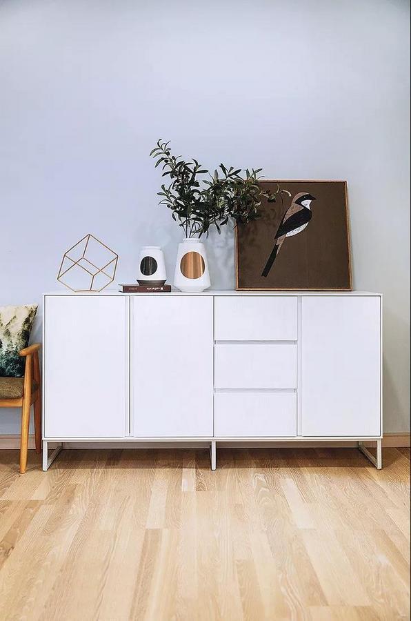 入户左侧设置了简易的玄关柜,方便收纳常用的鞋子。白色玄关柜线条简洁,搭配精致的装饰品,瞬间提升品位。
