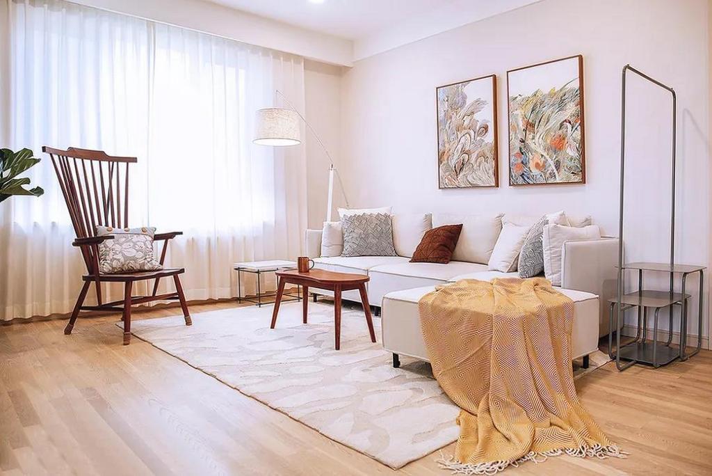 阳光透过白色窗帘柔和的洒进来,使室内更加通透敞亮。沙发一侧设置了别具一格的简易衣帽架,与下方双层边几连为一体,实用又独特。