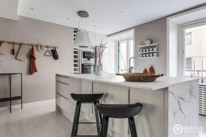开放式的厨房因为岛台而多了北欧的情调,设计师借墙面将收纳也做了精巧地设计,为空间的开放式设计做了优化,让实用与美学兼并起来。
