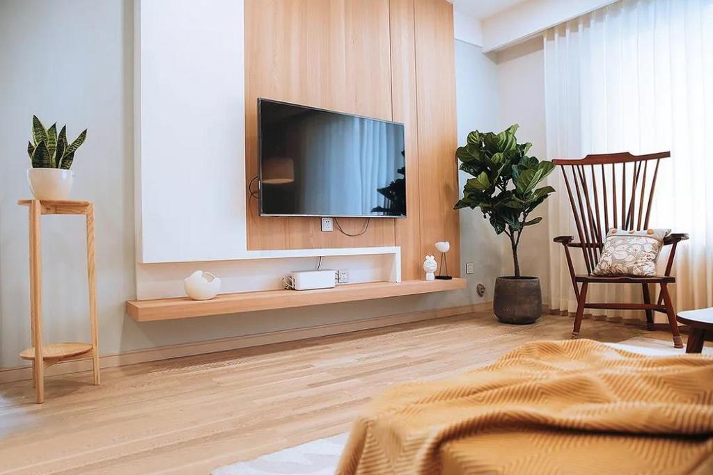 电视背景墙做了悬空设计,木质地板上墙,与白色一起将墙面分割,避免了色调上的单一性。