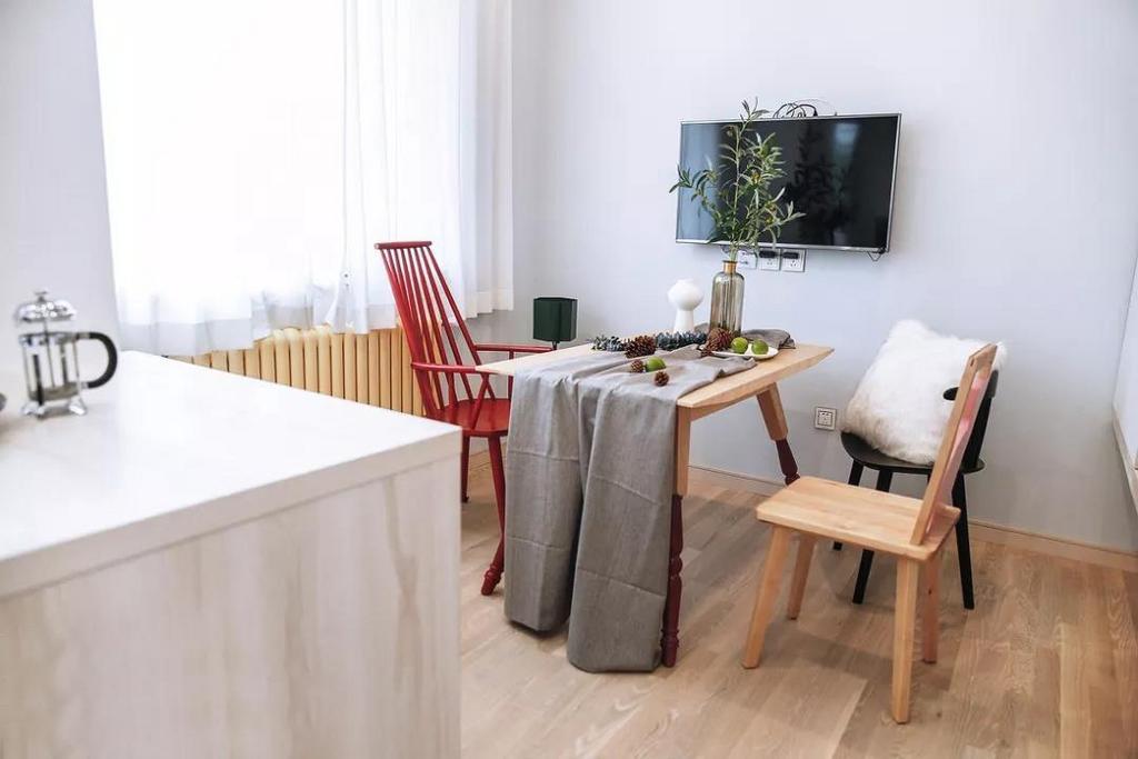餐厅色调清新,浅灰色桌布搭配木质餐桌,营造慵懒舒适的用餐空间。三只款式色系不一的餐椅摆放在一起,随性又有趣。