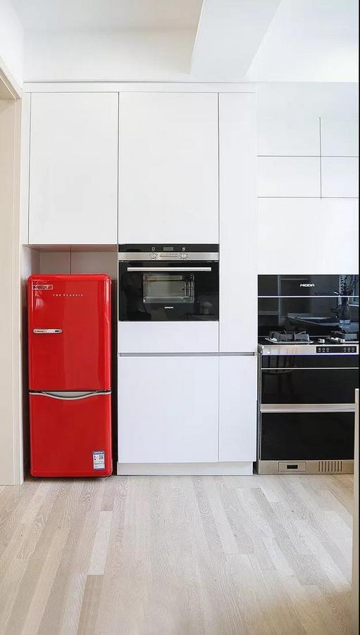 纯白空间里,冰箱的一抹亮丽的红让人猝不及防,惊艳十足。嵌入式的设计整齐利落,大写的赞。