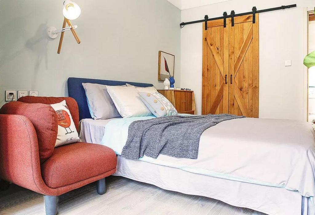 主卧风格清新雅致,嵌入式的衣柜选用了造型古朴的谷仓门,红色沙发复古气息十足,颜值爆表,搭配上方的床头灯,满满的时尚感,营造超有格调的阅读区。