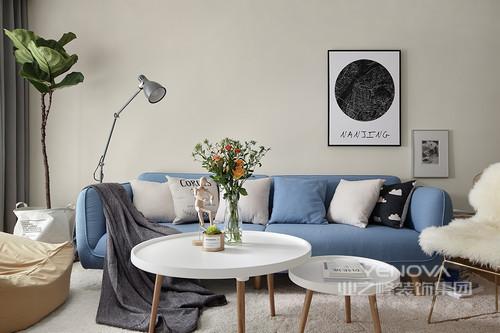 客厅以对称的技巧协调着家具之间的比例,调和出简单的温馨;蓝色沙发上白色靠垫点缀出清新感,轻巧的北欧白色圆几因为花卉点缀出自然风气;墙面上黑白画作与白色地毯在个性座椅衬托中更显时尚。