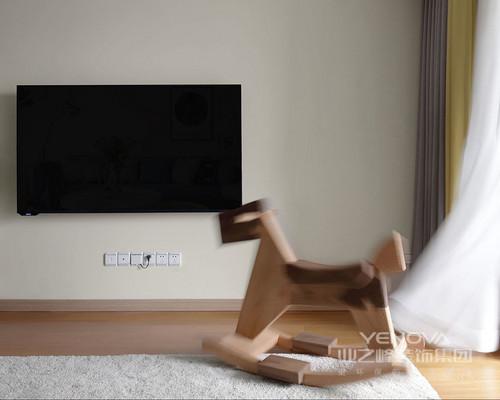 客厅以米色漆粉刷墙面,与木地板营造出中性质朴,让人回归淳朴,体会静谧;电视悬挂在墙面,与白色地毯都成色彩上的对比,木马带着童趣,显出活力,让生活更显自在。