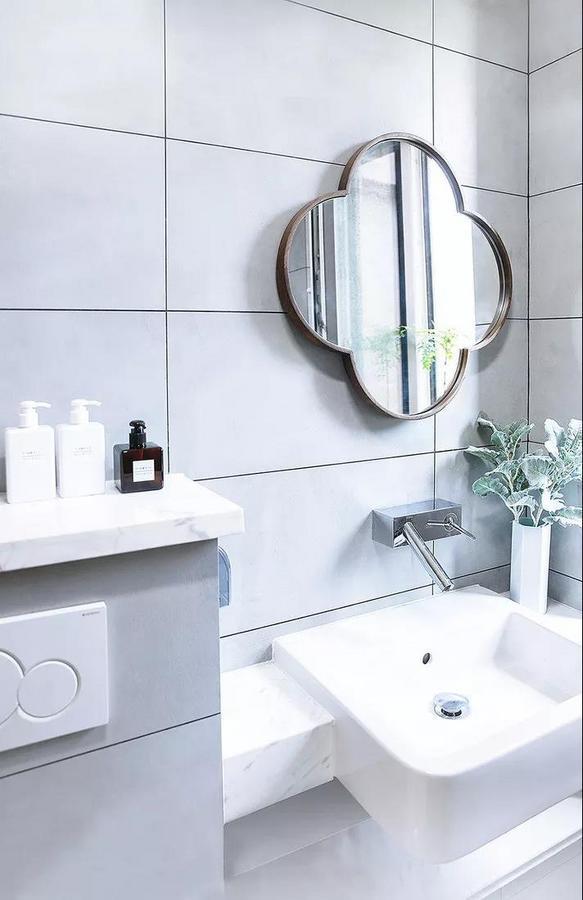 卫生间以灰白色搭配,简洁不失格调。镜子造型优雅别致,角落放一株绿植,增添清新的味道。