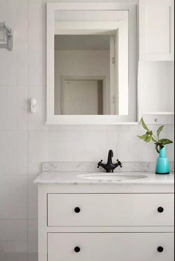 卫生间,白色浴室柜与镜柜延续了整体北欧格调的简约清新。