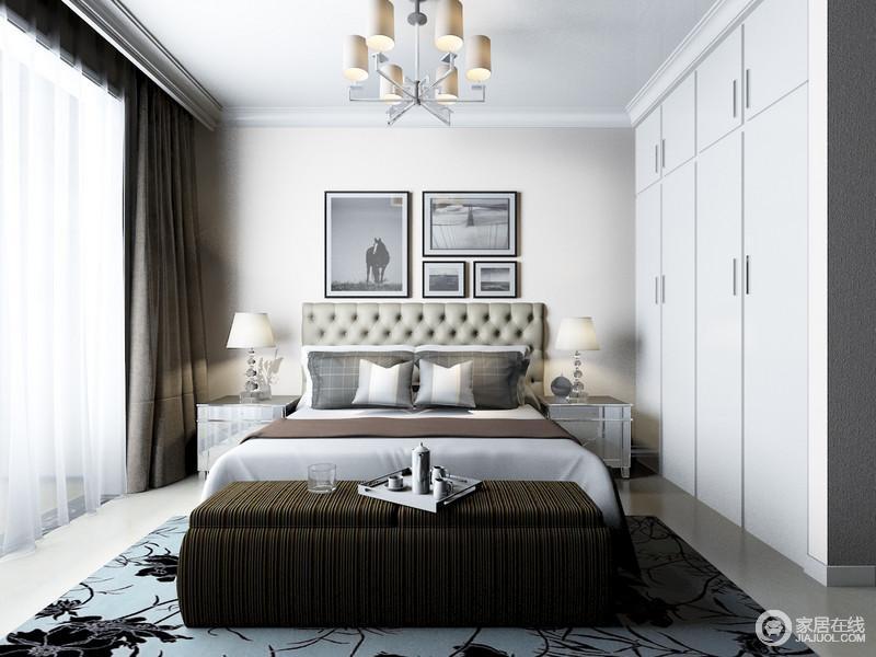 卧室白色的吊顶通过踢脚线做了墙面的加固和细化,强化了空间的几何结构,并与白色的衣柜造就规整和简约,灰色的墙面因为黑白摄影作品跳跃着黑白艺术,多了现代时尚;罗马纽扣式床头搭配银色金属窗头柜组合出现古典摩登,深绿色条纹座榻与灰色系软装做到视觉上的冲突,跳跃着生活的温情。