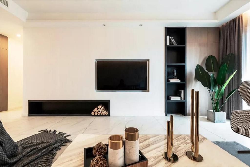 电视背景墙错落的壁龛增加收纳性的同时,也提升了空间设计感,原木色柜门与绿植传达环保的生活理念。
