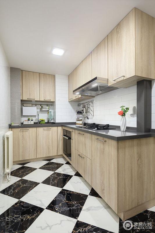 L形布置的厨房,操作很方便;黑白色系的地板、白色墙砖和黑色台面与木色橱柜搭配,营造出简洁又清新的厨房。