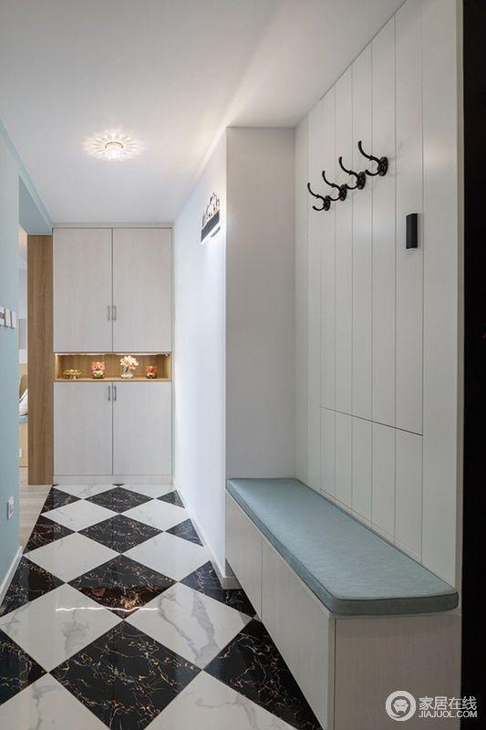 门厅地面铺以黑白棋格地砖,使视觉延展至玄关柜;上下组合式的置物柜中央,放置了摆件和萌物,渲染出几分趣味情调;转角墙面设计了卡座,白色护墙板缀以挂钩,使出入换鞋和挂物,都非常好用。