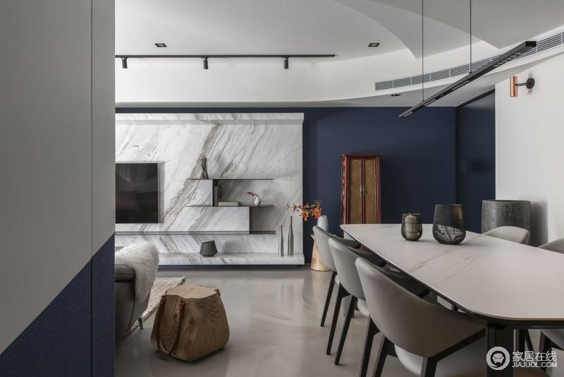 虽然空间黑白灰为主,但是,因为选材的精妙,让整个空间多了艺术感;背景墙以石材为主,借其文脉表达天然去雕琢的朴质,深蓝色漆粉刷的墙面与之形成冲撞,也带来一种色彩时尚;木柜的炫彩,与简约木几上的花器演绎器物带来的灵气,让生活看似简约,却颇有质感。