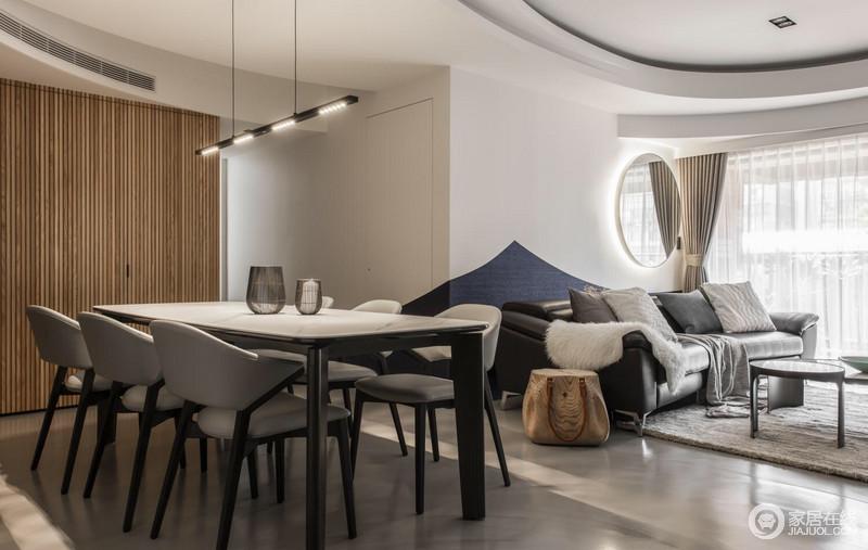 餐厅以白色为主,搭配灰色水泥地面,奠定了空间沉寂、空灵的效果;简约的餐桌因为灰色餐椅更为现代,铁艺金属镂空摆件与吊灯装饰出工业时尚;另一面墙包裹了原木板材,并以嵌入式的设计增加实用性,增加了空间的木意温和。