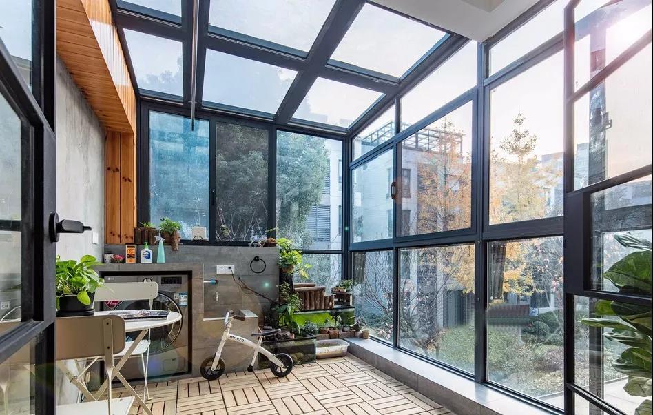 入户露台设计了大面积的玻璃门窗,把自然光线引入室内,黑色框架平衡了浅色空间的调性。