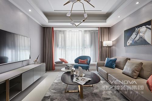 客厅粉刷了浅灰色漆,挂画点缀,素静中多了一丝稳重;驼色沙发因为彩色靠垫不显枯燥,吊灯、黑白金属圆几与蓝色扶手椅调和出现代时尚,跳跃中显得精致而简约,透露着浓重的设计感