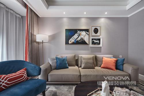 客厅以大量简单纯色家具来呼应灰色,让空间中性之中没有繁复,没有杂念,十分沉寂;蓝色和橙色靠垫点缀,与墙上的骏马图构成一种时尚的格调,优雅中不乏灵动,贵气中又不乏自然