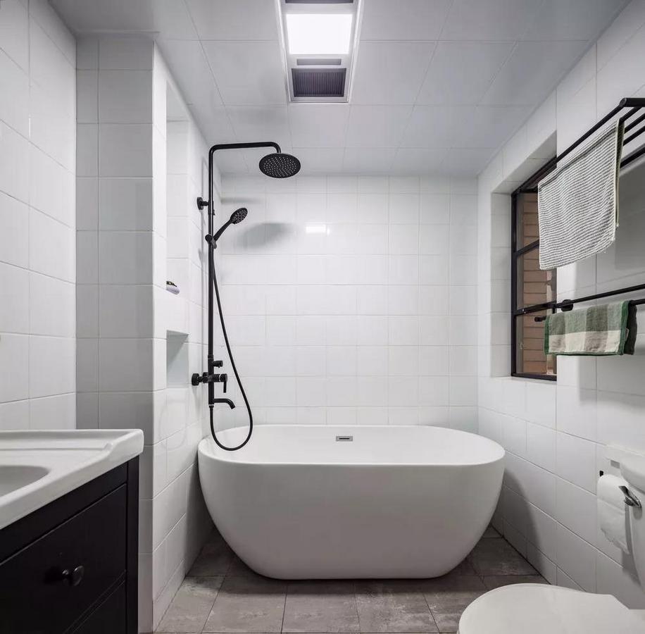主卫空间透着股干净凌冽的酷劲,椭圆形的独立浴缸一侧设计了壁龛,不仅可以增加收纳空间,也显得很有格调。