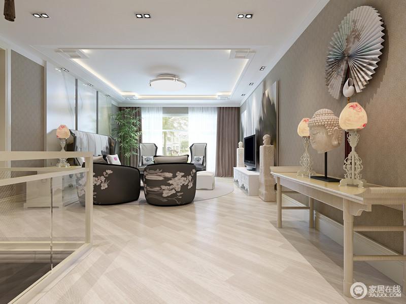 客厅宽敞而开放的格局自带空间感,不管是原木地板营造的自然朴质,还是深灰色壁纸的暗纹设计,都让空间内敛而宁静;新中式岸几上的中式木质台灯、如来饰品及折扇,缓解了空白感,多了中式文化气息。