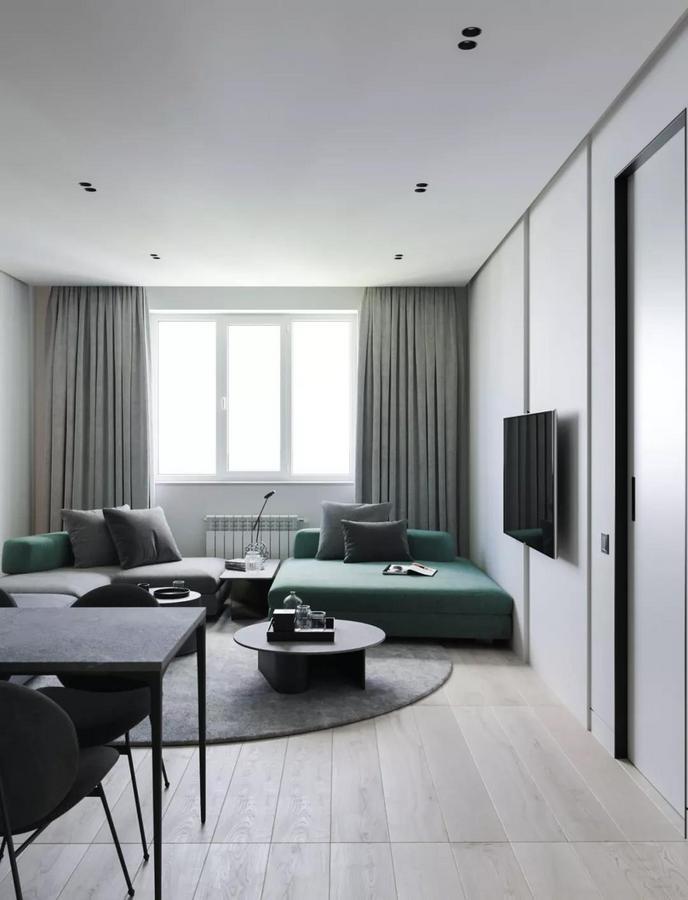由高级灰与墨绿色组合成的 U型大沙发 搭配着中间的圆形地毯 围合出一个舒适的休闲区域 让小房子显得更加有气场