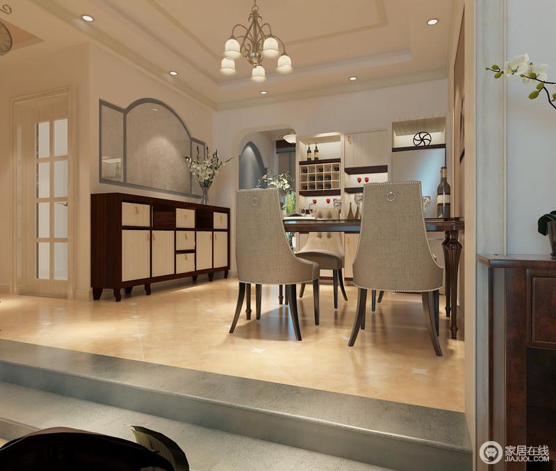 餐厅与客厅因为石阶自然分区,让开放式的空间具有明确的格局感;设计师并没有对空间进行大的改动,而是通过原本的结构将空间做功能化设计,不论是酒柜区,还餐厅区,田园与美式元素更显饱满,灰色铆钉餐椅的古典气韵,与美式实木收纳柜,让餐厅更为典雅。