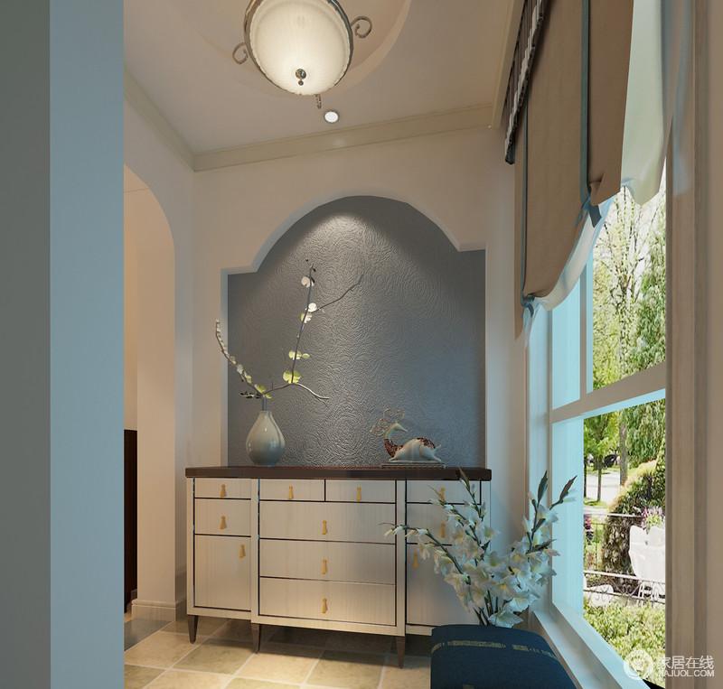 设计师并没有忽略空间中的每一个角落,在走廊的镜头,特地设计了一个休闲式收纳区,营造出一种和静惬意;拱形的石墙因为蓝灰色壁纸显得素雅,精致地玄关柜和蓝色坐凳组成优雅,让你在花香的芬芳中自得怡宁。