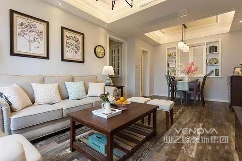 玄关进来右边是客厅,左边是餐厅。客餐厅都铺了木质地板,不同纹理的木质地板拼接在一起,提高了室内的层次感。深咖色的木质茶几放置在客厅中央,和浅灰色的沙发很搭