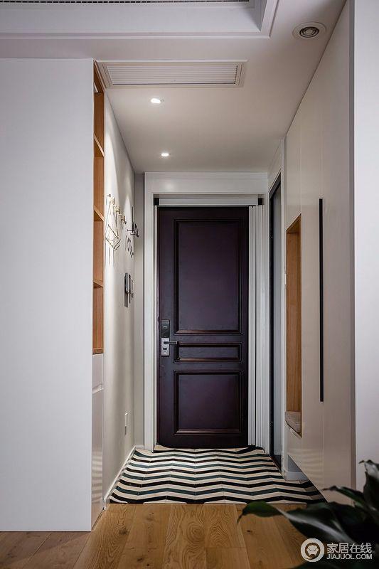 入户门充分利用两侧墙面,一侧内凹处设计成换鞋凳,另外一侧是格子置物柜;原木色与白色形成鲜明对比,换鞋凳卡座后面可以挂些日常衣服;整体玄关柜悬空,形成落灰在一处,底座的kd板是可以移动的,这样就可以保持鞋柜干净并不潮湿,底座设计有透气孔,增加鞋柜的透气性。