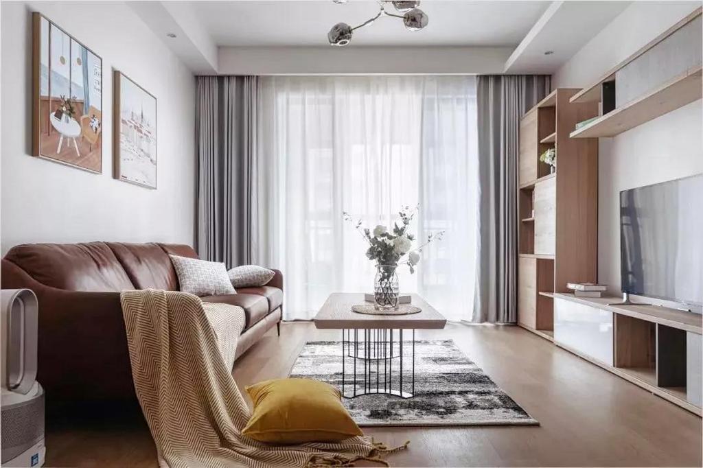 客厅整体以暖色系与清新的木质为主调,呈现出自然明亮的空间氛围。