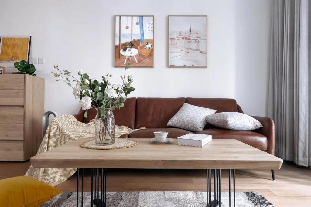 棕色皮质沙发质感满满,配以素色抱枕以及线条利落的茶几,沉稳而时尚。两幅简约精致的装饰画,布置出文艺优雅的惬意感。