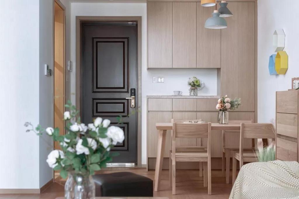餐厅原木质感的餐桌椅,搭配墙面的蓝白黄三色格架,以及粉蓝灰三色吊灯,为木质的空间带来了活泼跳跃的感觉。