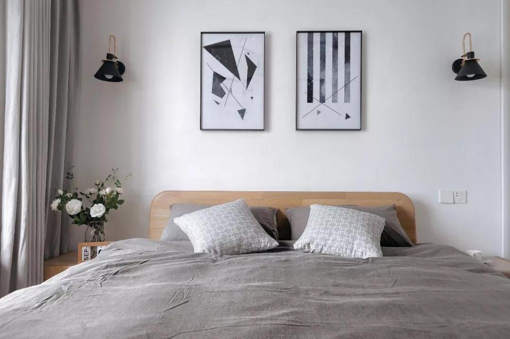 次卧以灰白色为主调,床头背景墙的黑白几何装饰画简约利落,两侧还有黑色的壁灯,整体简约不失清新,现代不失优雅。