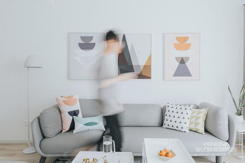 沙发背景后面挂着三幅附有艺术感气息的挂画