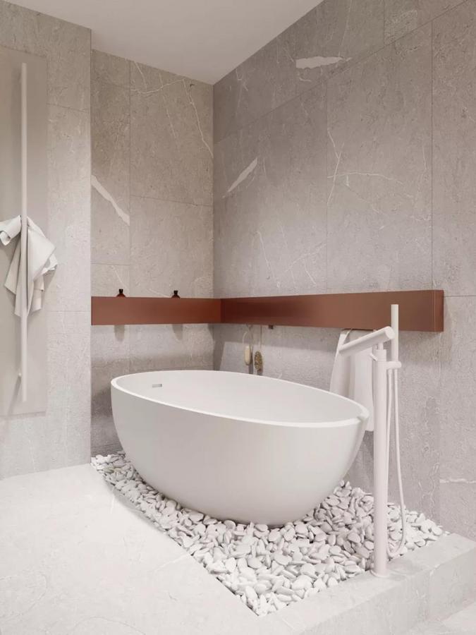 最里面的角落处放置了独立浴缸, 下面铺设白色的小石子, 并用赭色装饰板提供简单的收纳, 再一次流露出女主人对于精致生活的追求。