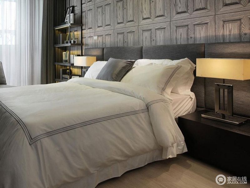 卧室的背景墙以深灰色为主,加重了空间的成熟,而几何的效果让原本简洁的空间多了动感,并与床品的色彩形成对比;方正的台灯造型得体,黄色暖光