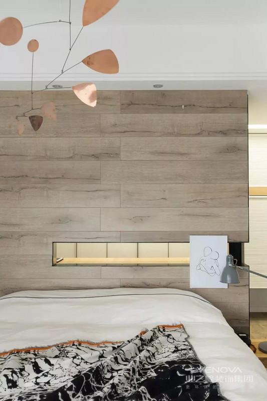 另一个卧室的床头以木纹砖上墙的设计,中间留空出一个置物层,内部装上藏光,层次丰富又美观。