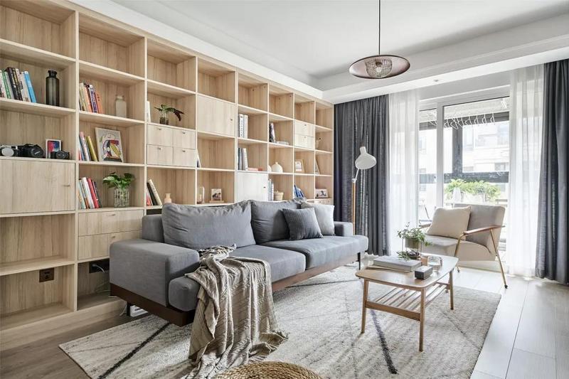 客厅整体以灰白色与木质为主调,灰色布艺沙发简约有质感,后方是一面木质书架墙,格外的实用有情调。