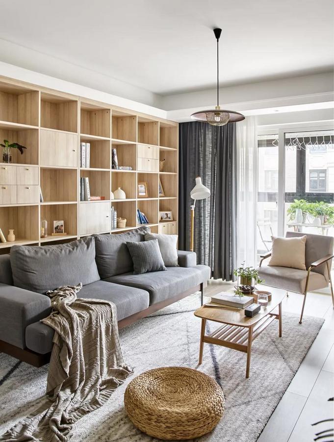 浅灰色地毯结合简易的木质茶几与休闲椅,还有一个编织蒲团坐垫,小小的空间也布置得轻松闲适。
