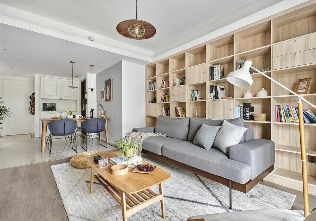整个沙发墙做成收纳展示架,一旁摆一盏落地灯,闲坐沙发上看书阅读、放松休闲,日子惬意自然。