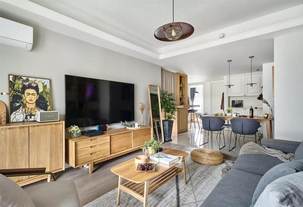 简洁的电视墙摆上成品电视柜与斗柜,整体木质感搭配装饰画与绿植,呈现出一幅清新自然的气息感。
