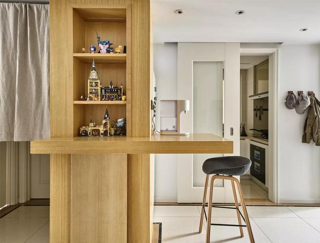 玄关过道区域结合墙面书柜设计了一个独特的小吧台,这里是各个空间的交集处,以独特的布置呈现出轻松闲适的生活态度。