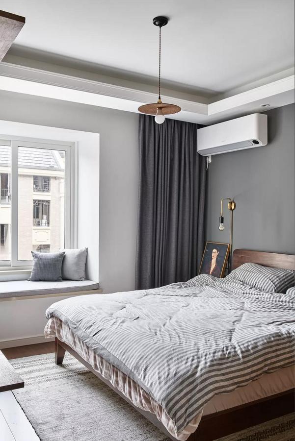 主卧以灰白两色为基调,配以深色木质大床与灰白条纹床品,营造静谧安逸的睡眠氛围。