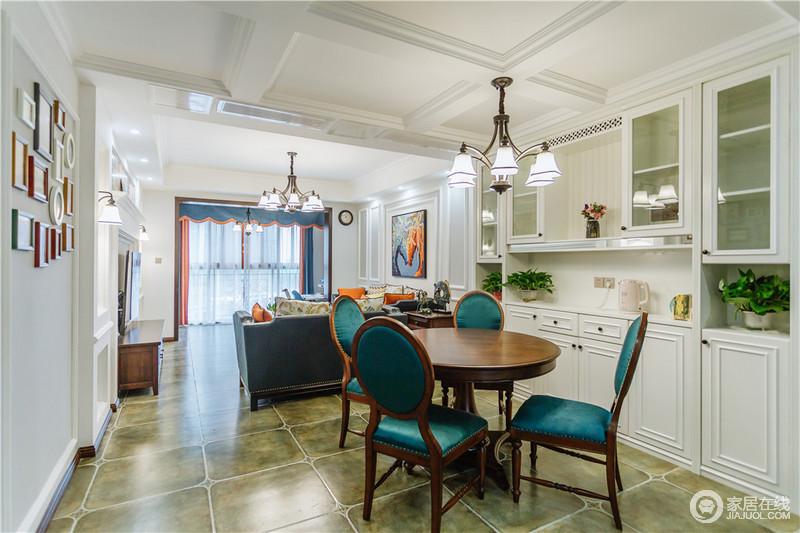 开放式的空间借几何吊顶和动线将客餐厅区分,并增加了白色储物柜,满足收纳的需要;美式胡桃木圆桌因为孔雀蓝的餐椅更显贵气,再加上美式铁艺吊灯的点缀,复古了不少。