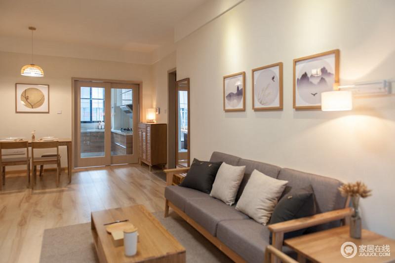 客厅白色的墙面因为几幅挂画的自然之景而清雅了不少,灰色实木沙发质地温实,与之形成雅致。