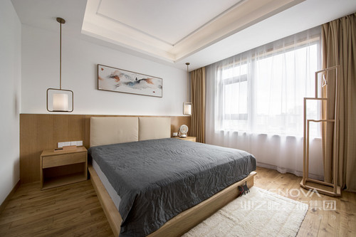 卧室更为极简,白色墙面与原木色地板,构成一种日式的和淡;就连窗帘和床软包都是相似地木色调,床头柜与吊灯和谐中增添实用性,白色纱幔与与灰色床品以对比让空间层次分明,温馨有致。
